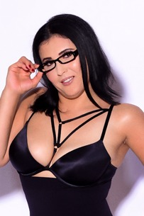 Erva stood up in front of a white background with her black glasses on and black body suit