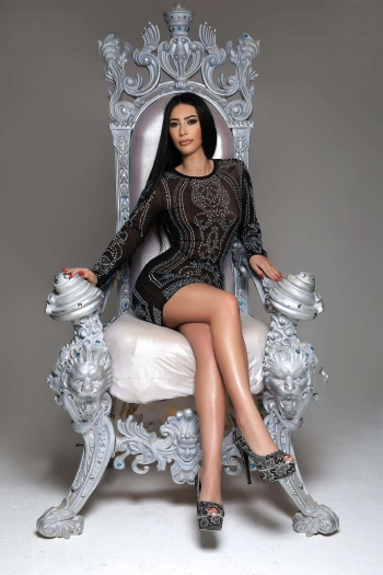 Alisha sitting on a throne wearing a patterned black dress