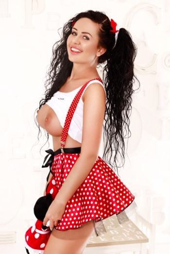 Amira wearing a white top and red and white spotted skirt with her breasts exposed