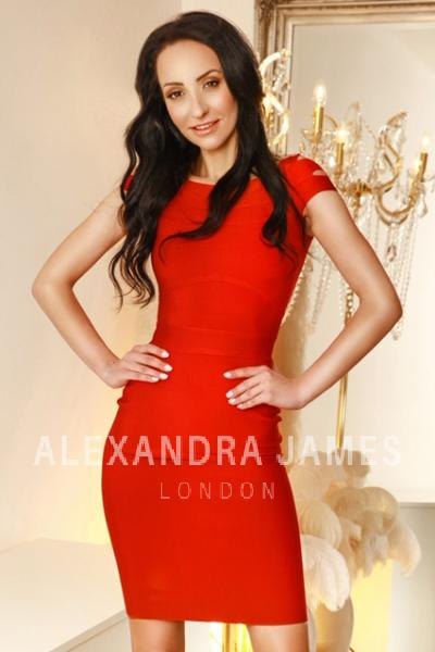 Jesi with her hand on her hips as she poses in a tight red dress