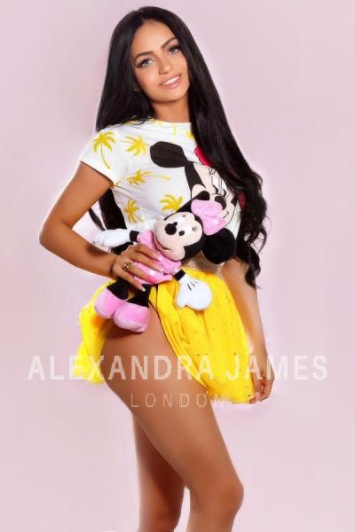 Bonita wearing a white and yellow Minnie Mouse top and a yellow skirt holding a Minnie Mouse toy