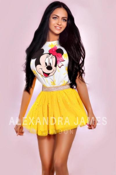 Bonita wearing a white and yellow Minnie Mouse top and a bright yellow skirt