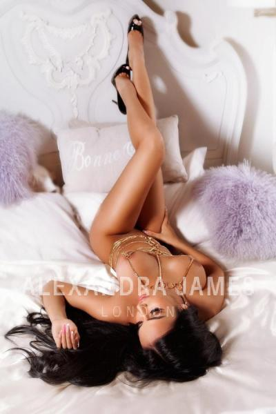 Bonita lying on a bed wearing only a golden chain dress and heels