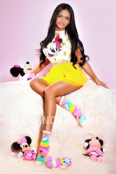 Bonita sitting wearing a Minnie Mouse top and yellow skirt surrounded by mouse toys