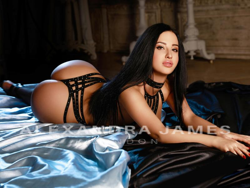 Melek lies on a blue silk bed and pouts seductively whilst wearing black studded lingerie
